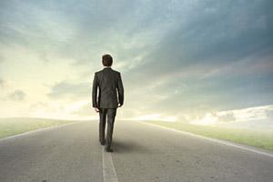 Uomo che percorre una strada guardando all'orizzonte
