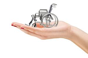 Mano di donna nel cui palmo vi è una carrozzina a rotelle